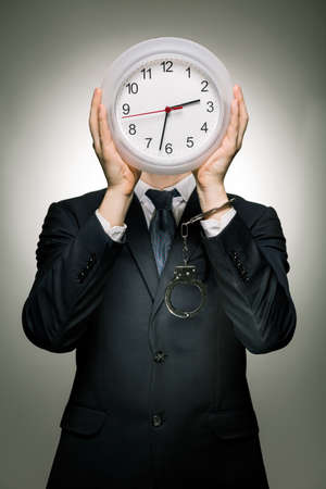 after hours: Young businessman in suit as a slave at work. On heads place big white clock Stock Photo