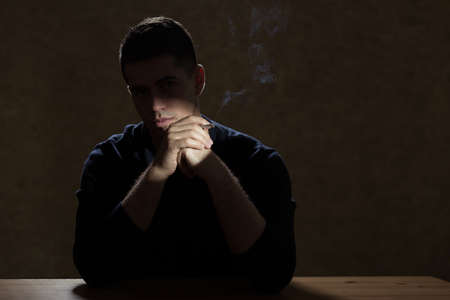 beside table: Young man smoking cigarette, sitting beside table in dark room