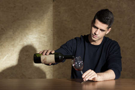 beside table: Man pouring glass of wine, sitting beside table