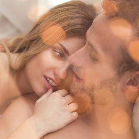 enamorados en la cama: Pareja joven durante romántica luna de miel en la cama Foto de archivo