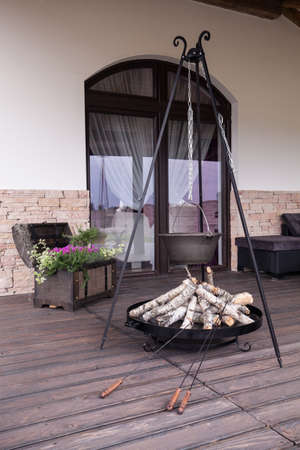 wood door: Cast-iron kettle and fireplace on wooden terrace Stock Photo