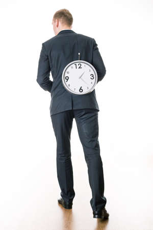 after hours: Tired young busy man in suit at work lifting the big clock. Man as a prisoner of time