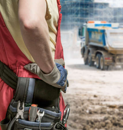 overseeing: Boss of builders in uniform overseeing employees work on construction site Stock Photo