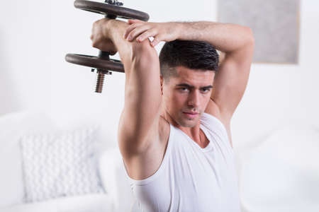 arm muscles: Fit young man strengthening arm muscles with dumbbell