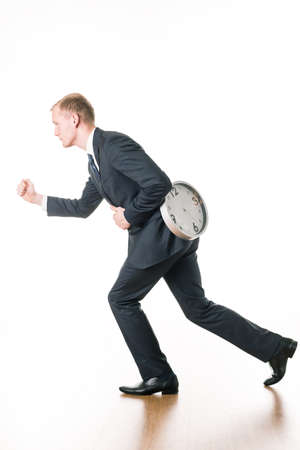after hours: Young businessman in hurry running to work. On back ticking clock Stock Photo