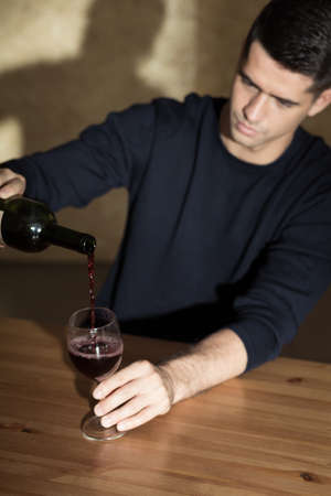 beside table: Man pouring glass of wine, sitting beside table alone