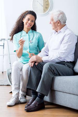 Caring jonge mantelzorger in uniform herinneren oudere man om medicijnen te nemen