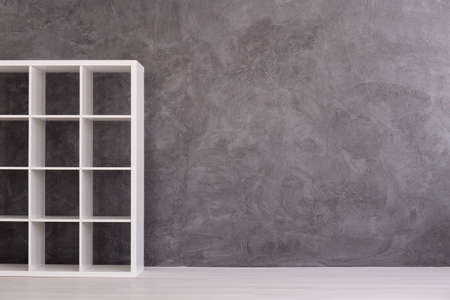 shelving: White, simple shelving unit standing in modern interior with light flooring and cement wall