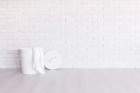White laundry basket standing in spacious room with light flooring and brick wall Stock Photo