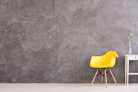 Nieuwe gele stoel en kleine decoratieve tafel in interieur met grijze muur Stockfoto