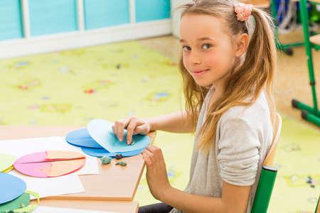 niños sentados: Foto de una chica joven que toma la clase de arte