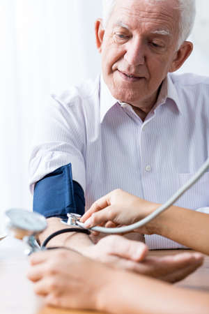 blood pressure gauge: Senior man with hypertension having regular blood pressure control