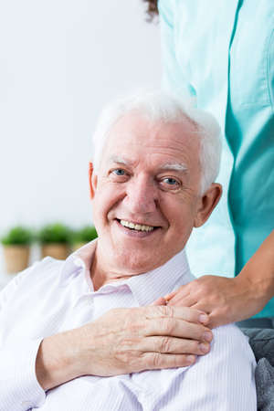 appreciating: Senior happy man appreciating help and care of his nurse. Holding his hand on caregivers hand