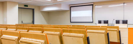 university classroom: Photo of row of wooden comfortable chairs on medical university. Classroom prepared for lectures