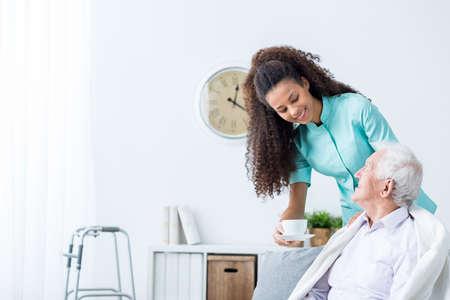 enfermeras: Bastante joven cuidador Taza de la porción de té por la tarde para el hombre de más edad feliz Foto de archivo
