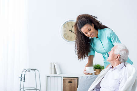 home care nurse: Pretty young caregiver serving afternoon cup of tea to older happy man