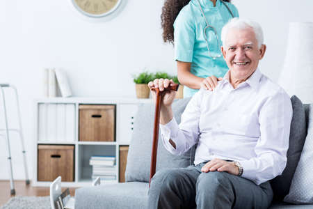 nursing assistant: Happy senior disabled man with walking stick and caring young nurse
