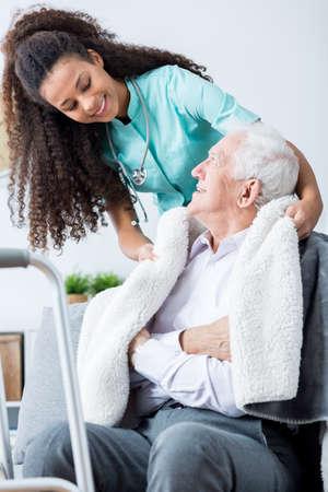 Jonge gelukkige verpleegster die troost haar oudere lachende patiënt