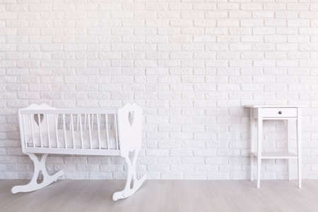 little table: White, wood cradle and little table standing in light interior with decorative brick wall Stock Photo