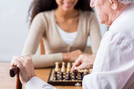 Close-up of older man's hand with walking stick. Man playing chess with young caregiver