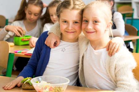 two girls hugging: Shot of two girls hugging in a classroom