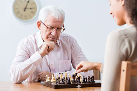 intergenerational: Senior smart man playing chess with young happy caregiver Stock Photo