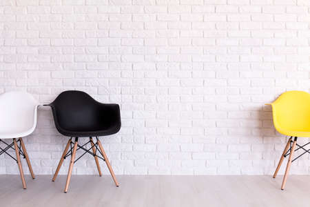 wall design: White, black and yellow chair standing in light interior with brick wall design Stock Photo