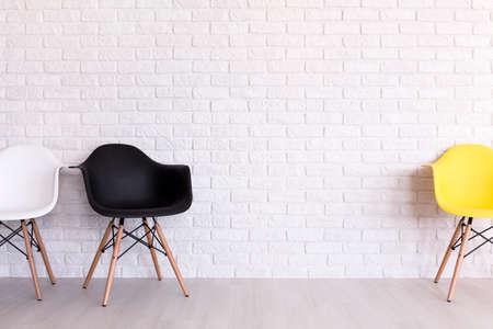 Witte, zwarte en gele stoel die zich in licht binnenland met bakstenen muurontwerp bevinden Stockfoto