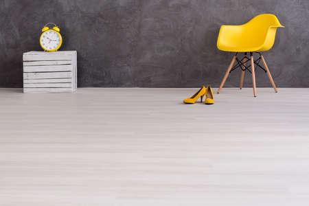 黄色い目覚まし時計、椅子、ハイヒール、光の床とセメントの壁をインテリアに木製ボックス立って