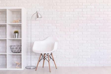 Witte regale met huisdecoraties, staand lamp en moderne stoel in een lichte kamer met bakstenen muurontwerp