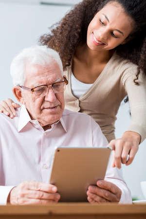 ancianos felices: hombre inteligente senior de aprender a utilizar las nuevas tecnologías. Bastante joven médico que ayuda al hombre a usar la tableta Foto de archivo
