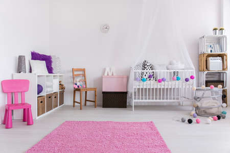 nursery room: Shot of a white nursery with pink accessories Stock Photo
