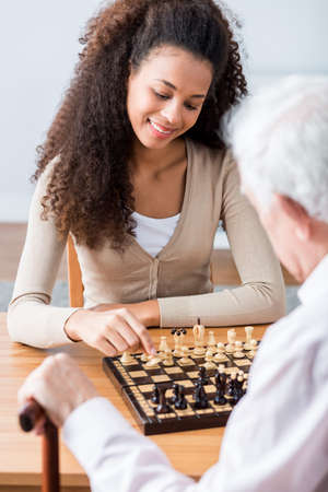 Young pretty happy carer plying chess with her older ward Фото со стока