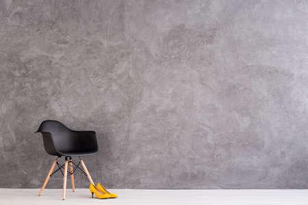 新しい黒い椅子とセメントの壁の設計で広々 としたインテリアに立って黄色のハイヒール 写真素材