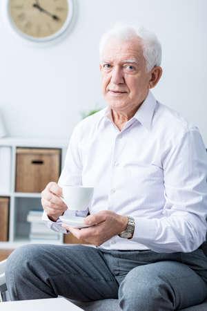 persona feliz: Hombre mayor feliz elegante que bebe té en la tarde. Sentado en una silla en su casa Foto de archivo