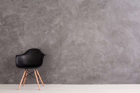 wall design: Modern,black chair standing in empty interior, cement wall design in the background Stock Photo