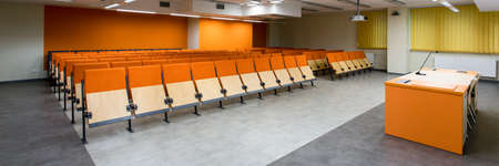 orange chairs: Rows of orange chairs in spacious leture hall with arble floor and new technology