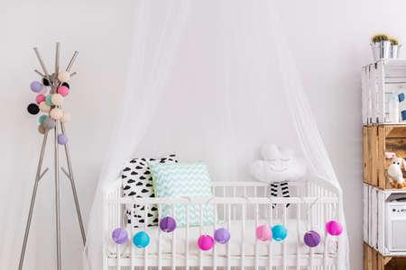 nursery room: Shot of a crib in a modern white nursery room