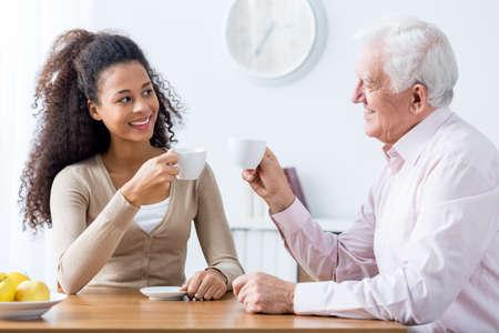 Jeune soignant heureux et souriant tasse homme potable senior de café ensemble à la maison