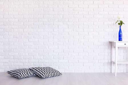 almohadas modelo decorativo, blanco y negro y una mesa pequeña de pie en el interior blanco con el diseño de la pared de ladrillo