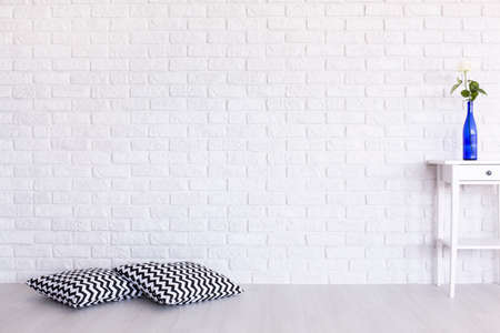 Decorative, black and white pattern pillows and small table standing in white interior with brick wall design Archivio Fotografico