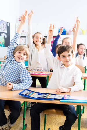 schoolroom: Shot of a group of students raising their hands in a classroom Stock Photo