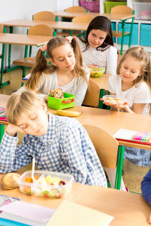 schoolroom: Shot of a bored little boy sitting in a classroom and looking at his food Stock Photo