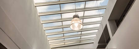 modern building: Close-up of little lamp hang by the ceiling in spacious college building