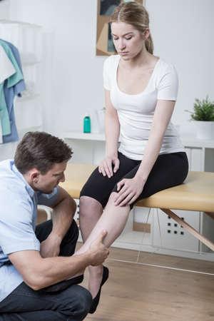 splint: Paciente con calambres en las piernas en el consultorio del fisioterapeuta Foto de archivo