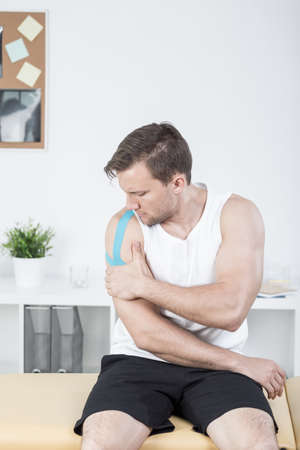 physiotherapists: Sporty man with arm injury at physiotherapists office