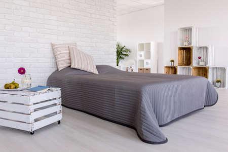 Chambre lumineuse et spacieuse avec un mur en briques blanches, un grand lit et une table de chevet fait à la main en forme de boite en bois