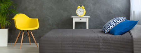 bedcover: Panorama of a modern bedroom with large, yellow alarm clock on a nightstand beside a grey-covered bed