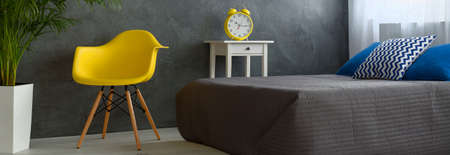 bedcover: Panorama of a modern bedroom with grey stucco wall, grey-covered bed and yellow designer chair Stock Photo