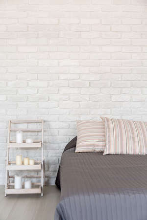 interior room: Light bedroom with white brick wall, large bed and handmade nightstand Stock Photo